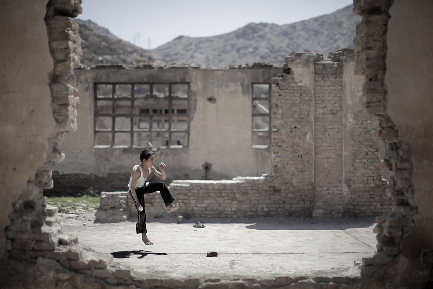 An Afghan boy runs up to bowl