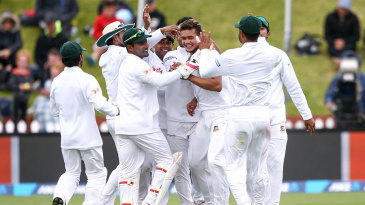 Taskin Ahmed is surrounded by team-mates after claiming Kane Williamson for his maiden Test wicket