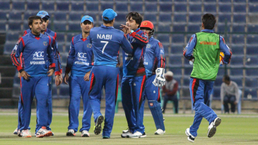 Rashid Khan gets a high five from Mohammad Nabi after dismissing Kevin O'Brien