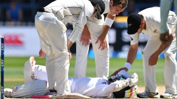 New Zealand players check on Mushfiqur Rahim after he was hit on the head