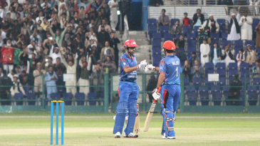 Karim Janat punches gloves with Najibullah Zadran after striking a boundary over midwicket