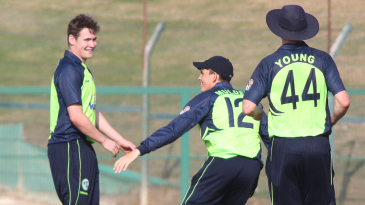 Joshua Little gets congratulated by Jacob Mulder and Craig Young dismissing Gerrie Snyman for his maiden international wicket
