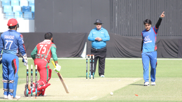 Rashid Khan points Khurram Khan back to the dugout after bowling him for 24
