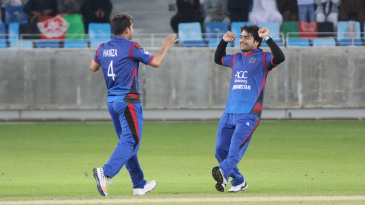 Rashid Khan rushes in to celebrate a wicket with Amir Hamza