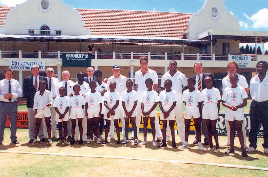Mike Atherton (back row, in cap) at the Harare Sports Club with a young Patrick Gada (front row, holding miniature bat) and coach Lazarus Zizhou (back row, fifth from left, with hands on a boy's shoulders)