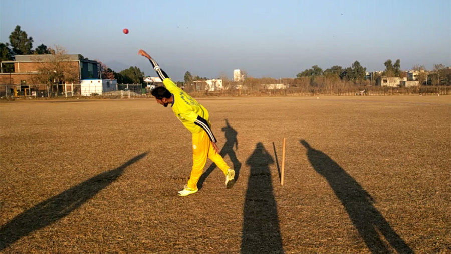 A club bowler bowls while wearing the CricFlex arm sleeve that measures elbow flex in bowlers