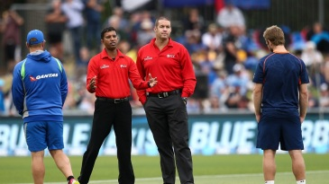 Umpires Kumar Dharmasena and Chris Brown speak to the two captains