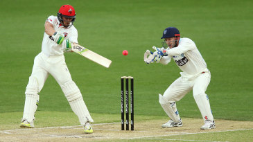 Alex Carey cuts the ball watched by wicketkeeper Peter Nevill