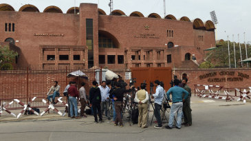 Media personnel wait outside the Gaddafi Stadium