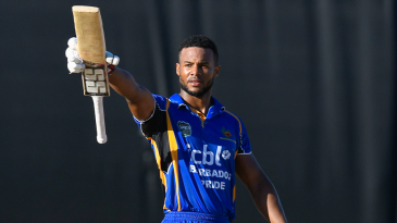 Shai Hope raises his bat after recording a century in the final
