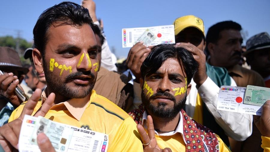 Peshawar Zalmi fans flash their match tickets as they queue up outside the Gaddafi Stadium