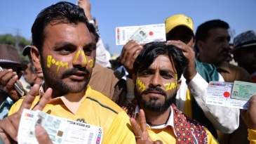 Peshawar Zalmi fans flash their match tickets as they queue up outside the Gaddafi Stadium