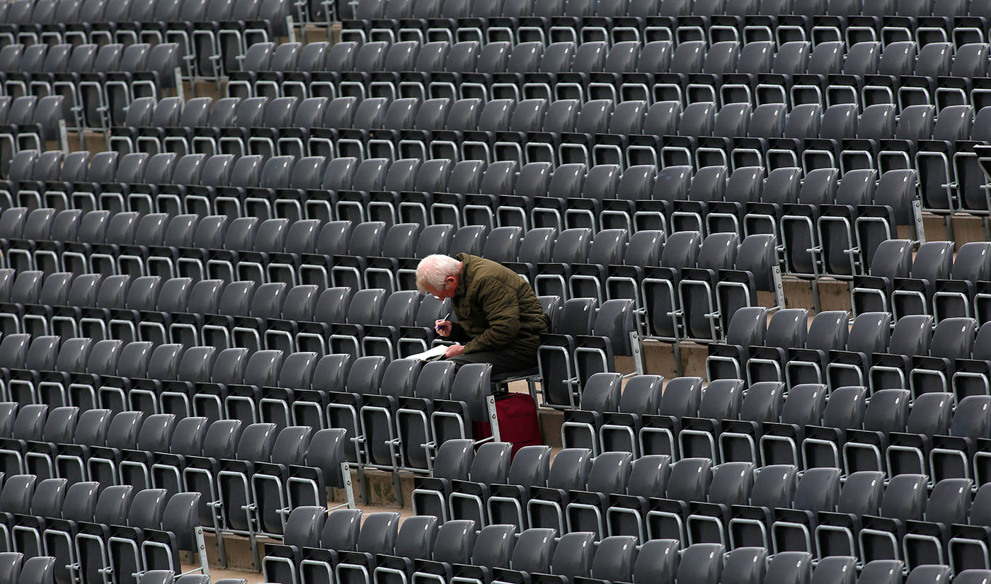 A spectator works on a crossword puzzle