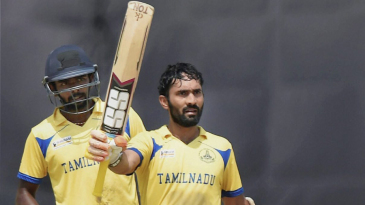 Dinesh Karthik raises his bat after bringing up his hundred
