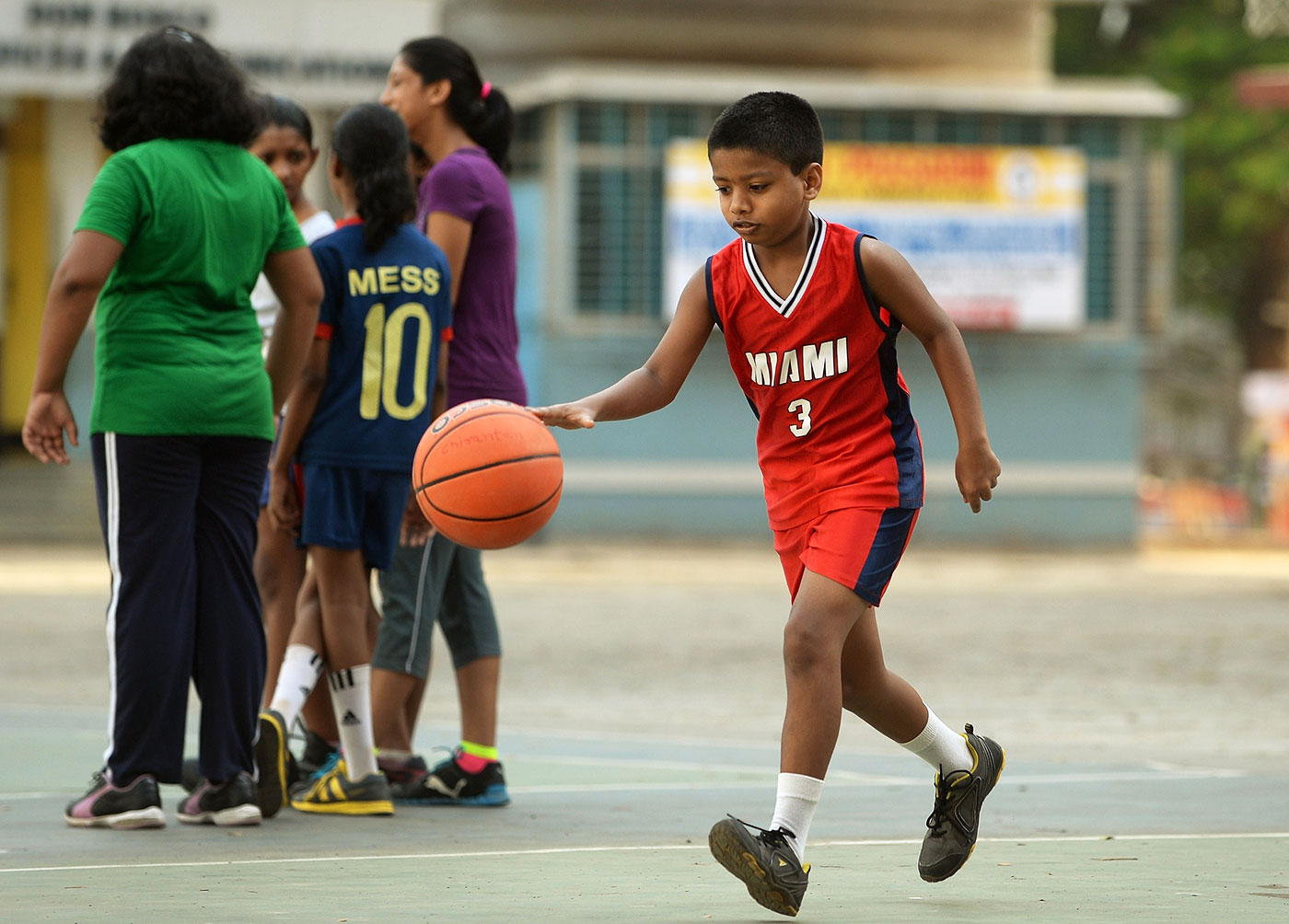 A child dribbles a basketball at a school camp