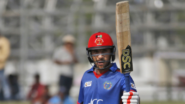 Rahmat Shah raises his bat after bringing up his half-century