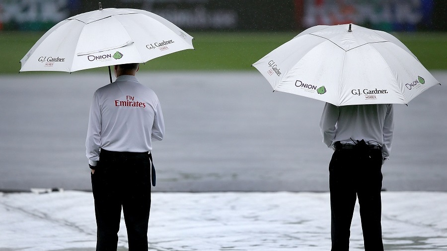 The umpires take shelter on a rainy day