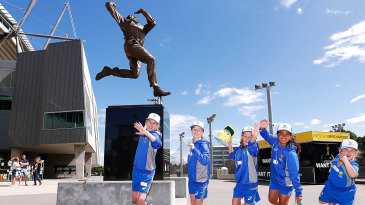 Young fans imitate Dennis Lillee's bowling action under his statue at the MCG