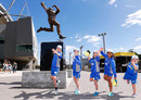 Young fans imitate Dennis Lillee's bowling action under his statue at the MCG, February 18, 2017