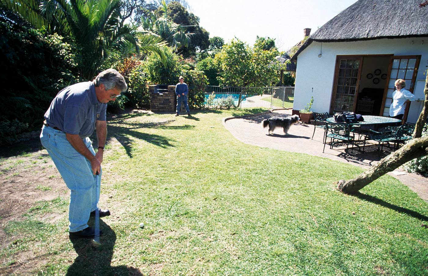 In happier times: Woolmer plays golf in the garden of his Cape Town home with his wife and son looking on