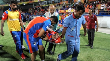 Andrew Tye is stretchered off after injuring his shoulder