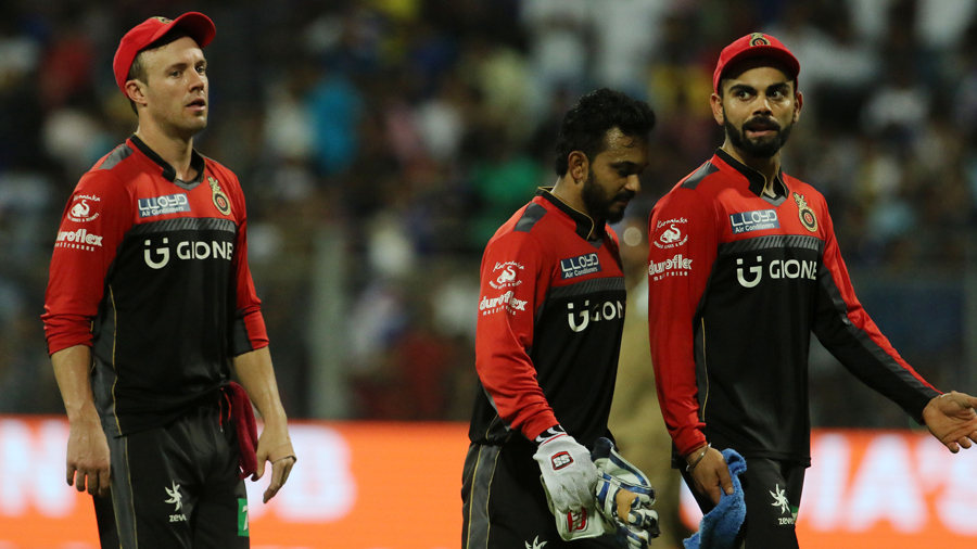 AB de Villiers, Kedar Jadhav and Virat Kohli walk off the field after the close of play