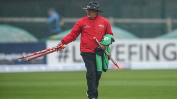 Umpire Ian Gould walks off with the stumps after rain interrupts play