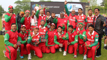 Oman Cricket director Pankaj Khimji (top row, middle) leads a chant after the team gained promotion to WCL Division Four