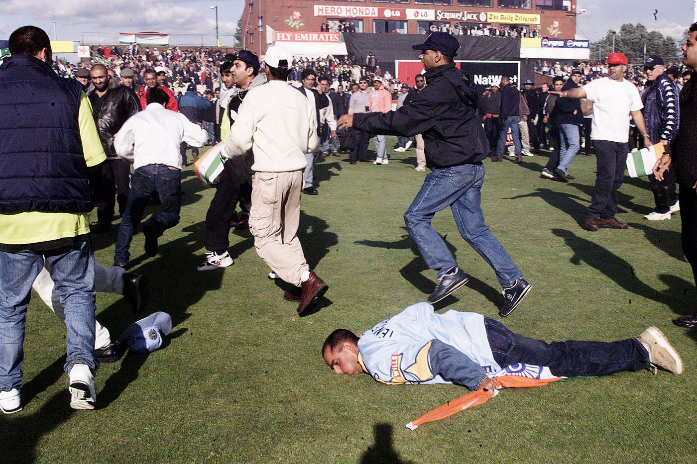 An India fan falls to the ground during a pitch invasion at Old Trafford during the 1999 World Cup game between the two sides
