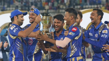 Rohit Sharma passes on the trophy to his delighted team-mates