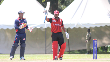 Dhanuka Pathirana raises his bat after reaching a half-century