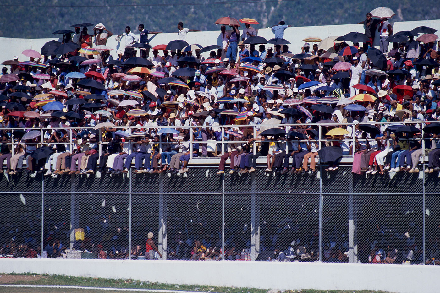 Spectators use umbrellas to shield themselves from the sun