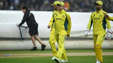 Australia's momentum was checked when rain interrupted with England three-down