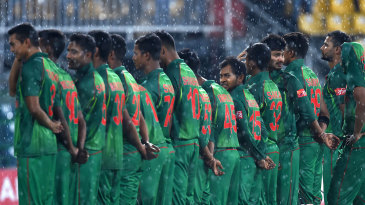 Bangladesh players stand for the anthems in the rain