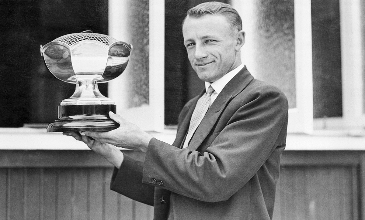 Donald Bradman holds up a trophy