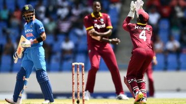 Virat Kohli watches and Jason Holder prepares to celebrate as Shai Hope gets under a catch