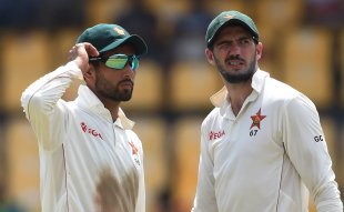 Sikandar Raza and Graeme Cremer confer on the field