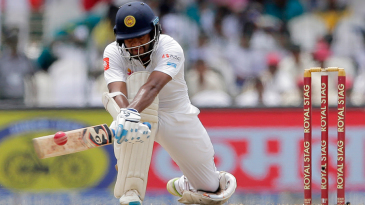 Dimuth Karunaratne lunges into a reverse sweep