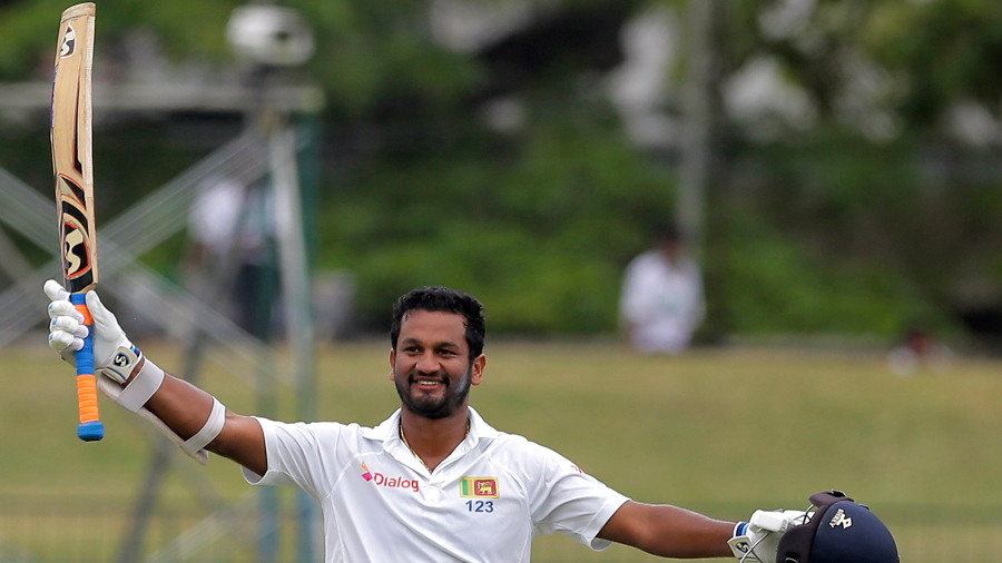 Dimuth Karunaratne raises his bat after notching up his sixth Test hundred