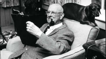 PG Wodehouse sits reading a book and smoking a pipe with a dog perched behind his chair