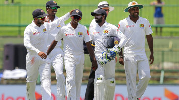 Lakshan Sandakan is congratulated by his team-mates on his maiden five-wicket haul