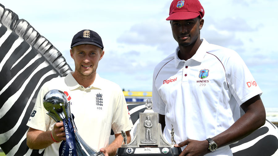 Joe Root and Jason Holder pose with the Investec series trophy and the Wisden Trophy