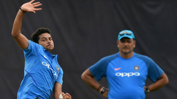 Kuldeep Yadav sends down a delivery as coach Ravi Shastri looks on