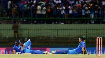 Rohit Sharma and MS Dhoni sit near the pitch as crowd trouble pauses the match
