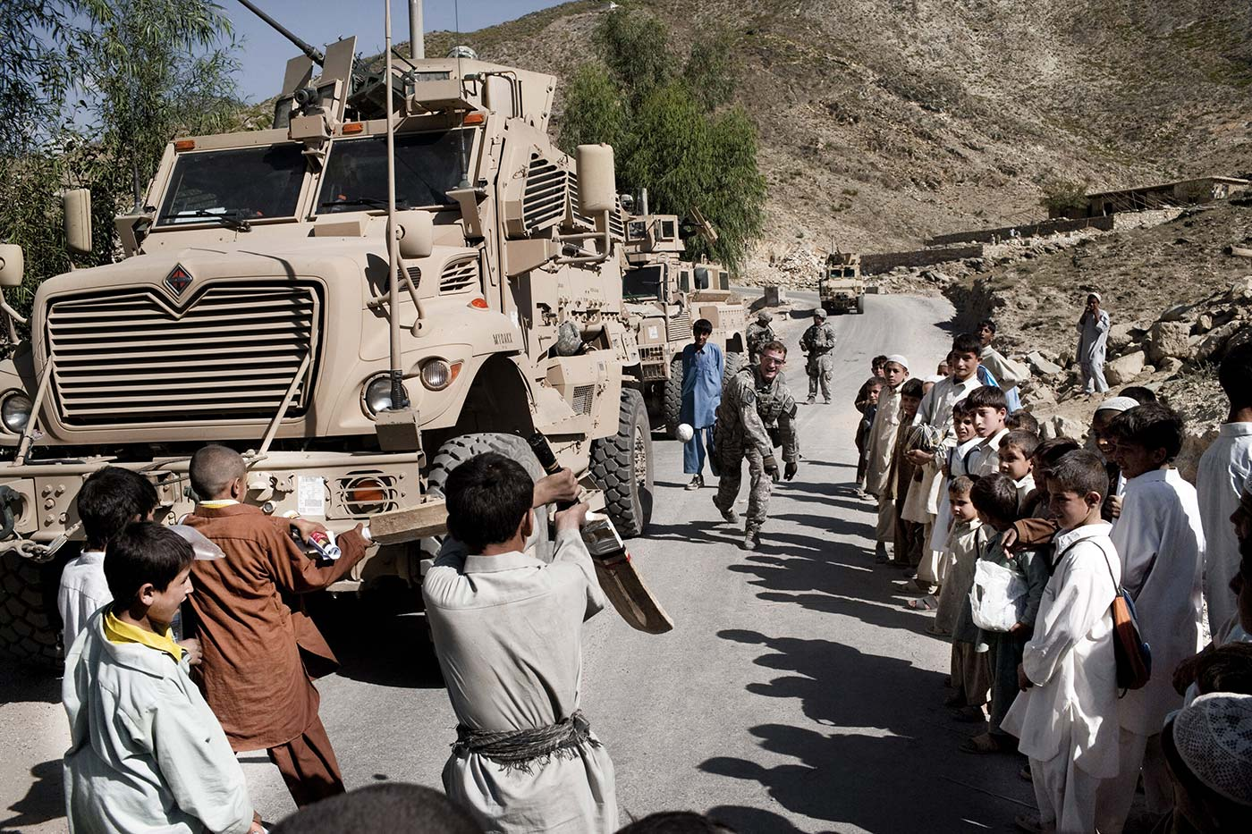 An American soldier plays cricket with local kids in Kunar province in 2009