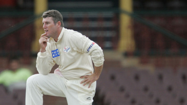 Stuart MacGill kneels in the field