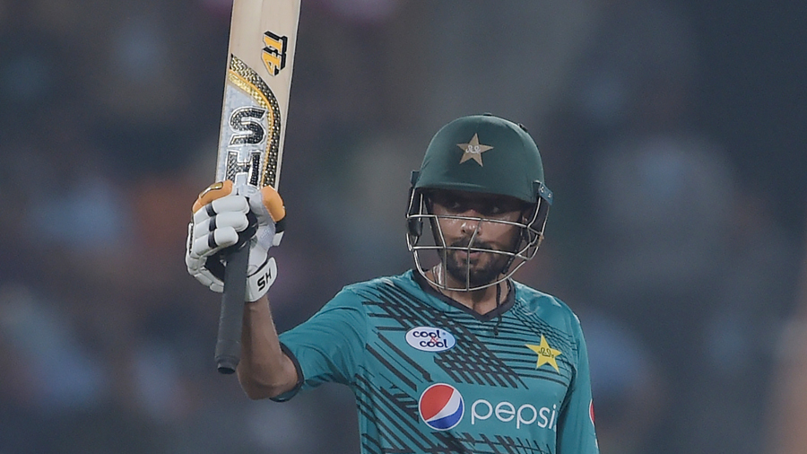 Babar Azam raises his bat after getting to his half century