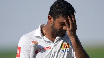 A dejected Dimuth Karunaratne walks off the field