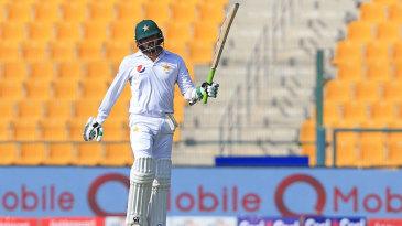 Azhar Ali raises his bat after his fifty