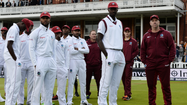 West Indies' players stand of the field with their coach Stuart Law at the end of the game